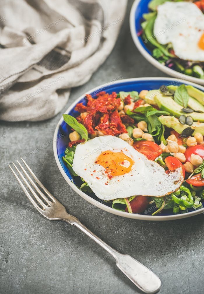 Vegetarian concept breakfast with fried egg, chickpea, vegetables, seeds