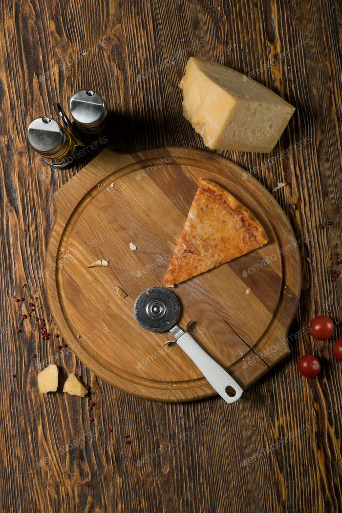 Slice of pizza, tomatoes, cheese, olive oil on a wooden table