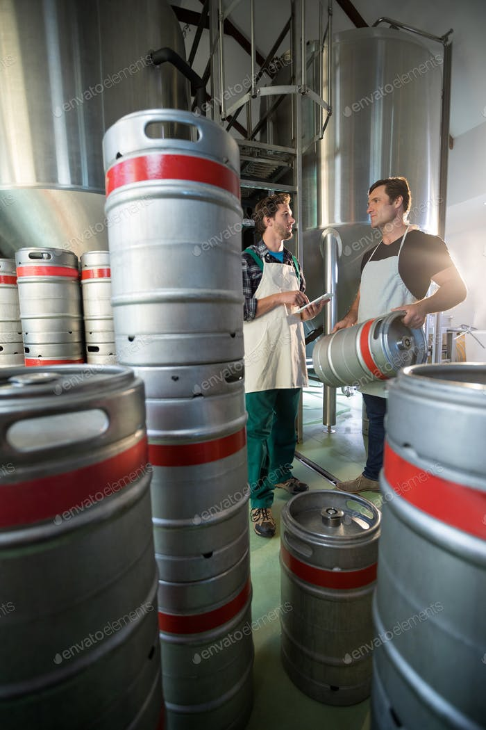 Coworkers discussing while standing by vats and kegs