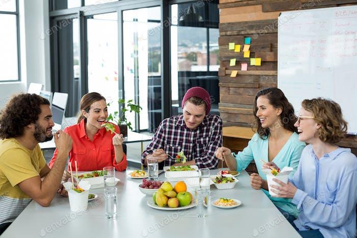 Lächelnde Business-Führungskräfte mit Essen im Büro