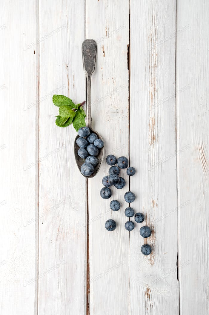 Blueberries in a vintage spoon on a white wooden table.