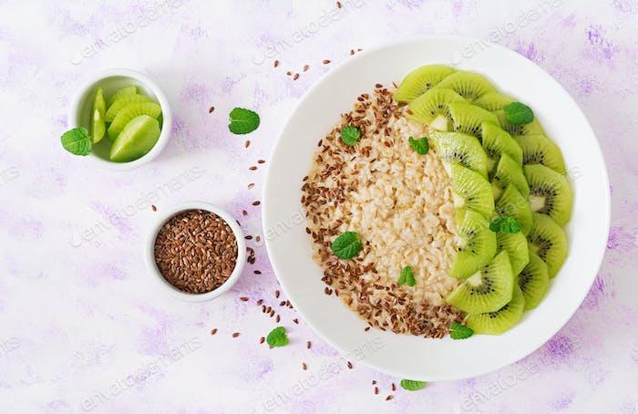 Tasty and healthy oatmeal porridge with kiwi and flax seeds.