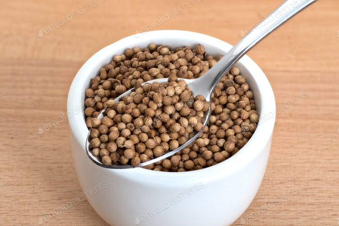 Coriander seeds spoon and in small white bowl