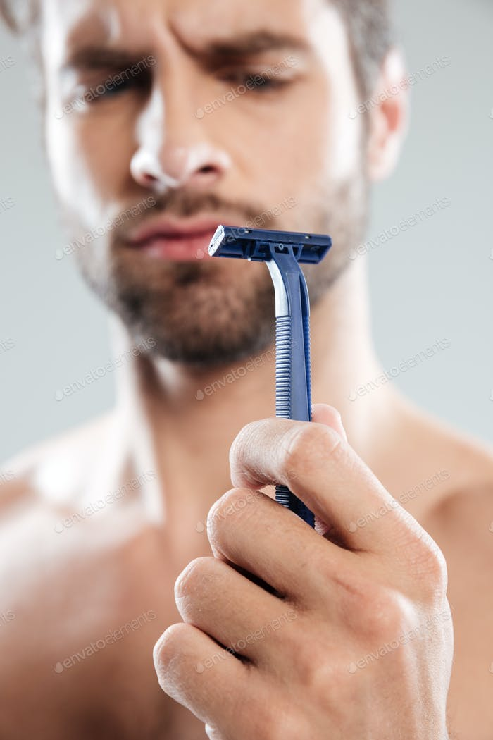Portrait of a doubtful concentrated bearded man looking at razor