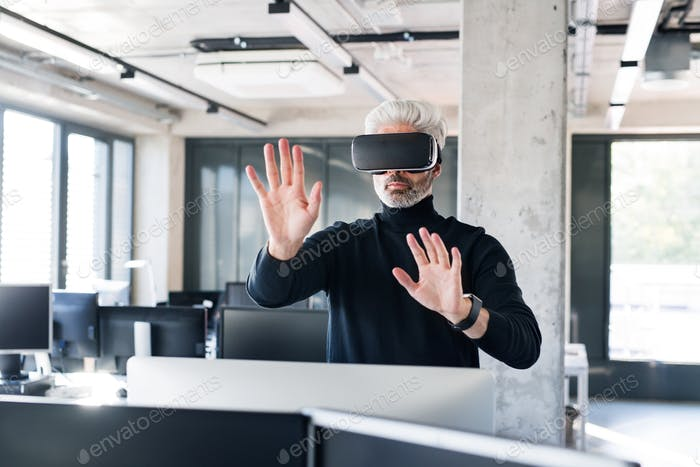 Mature businessman with VD goggles in the office.