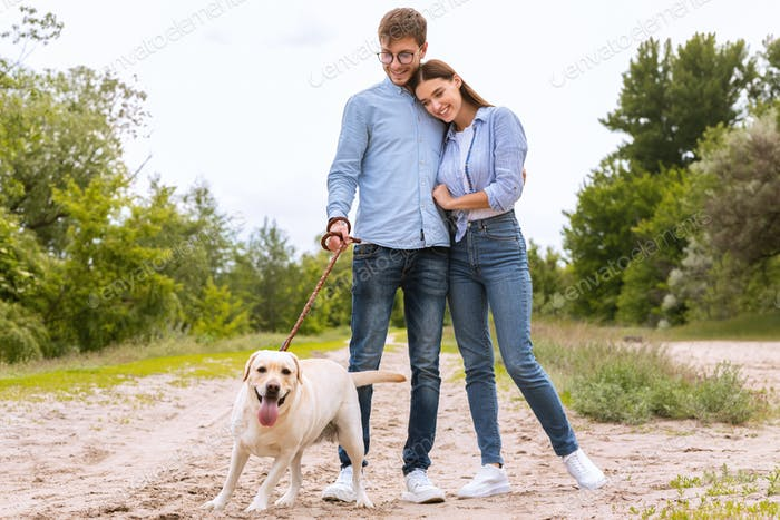 Portrait of happy young couple walking their lovely dog