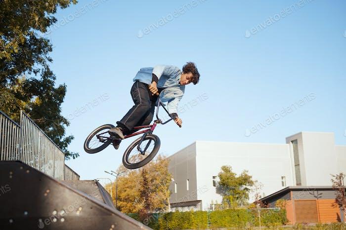 Biker BMX macho, salto en acción, skatepark