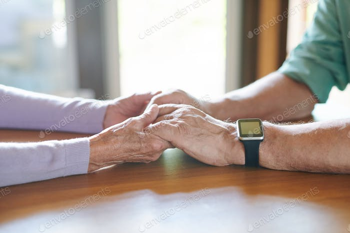 Affectionate and devoted senior spouses holding by hands