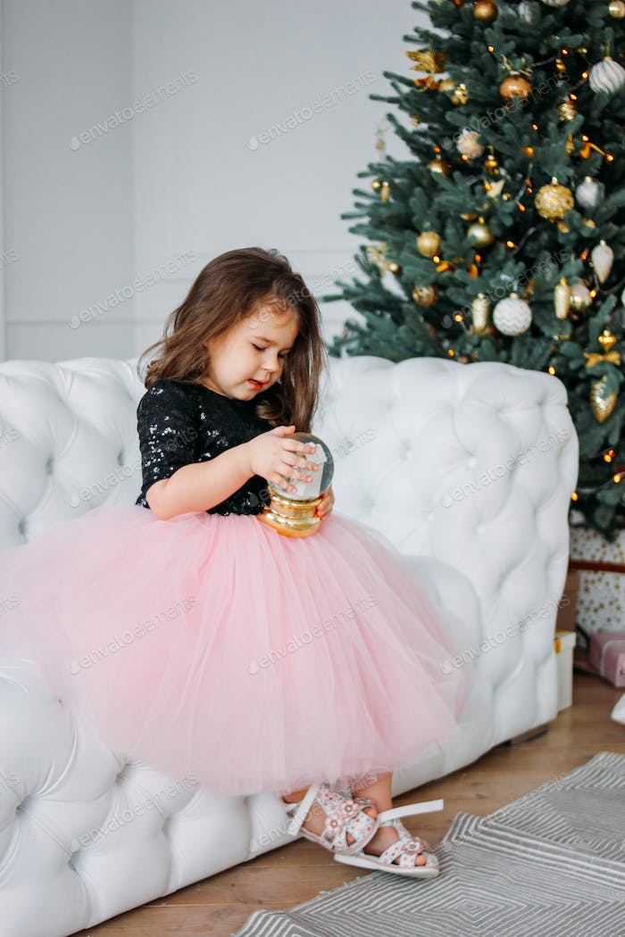 Little girl in dress tutu skirt with glass ball in living room on background of Christmas tree