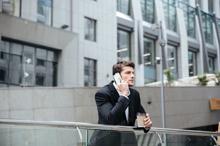 Businessman talking on mobile phone and drinking coffee in city