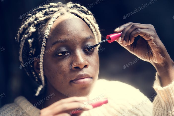 Black woman applying mascara