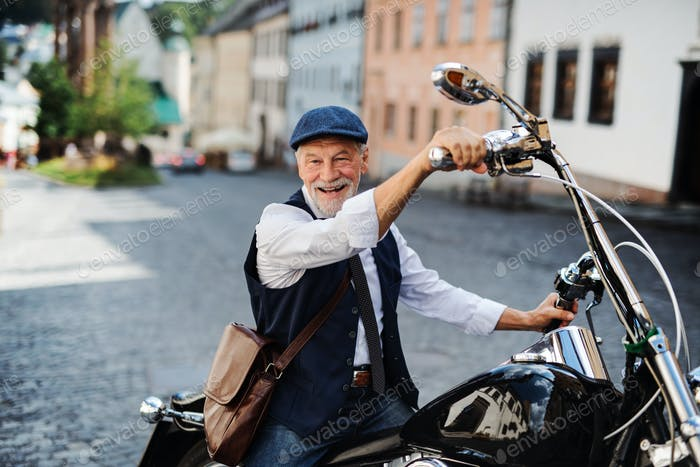 A senior businessman with motorbike in town