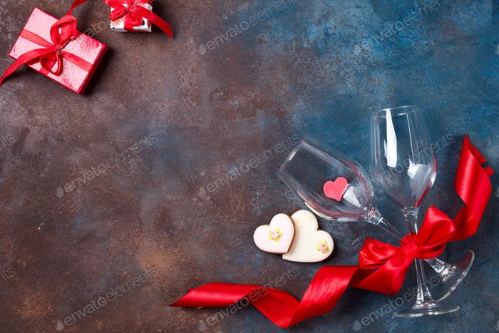 Composition with wine glasses, ribbon and decorative hearts on stone background with copy space