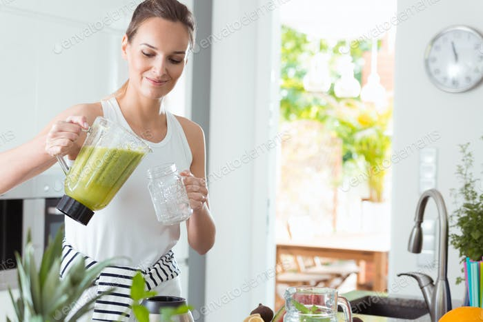 Woman pouring cocktail into jar