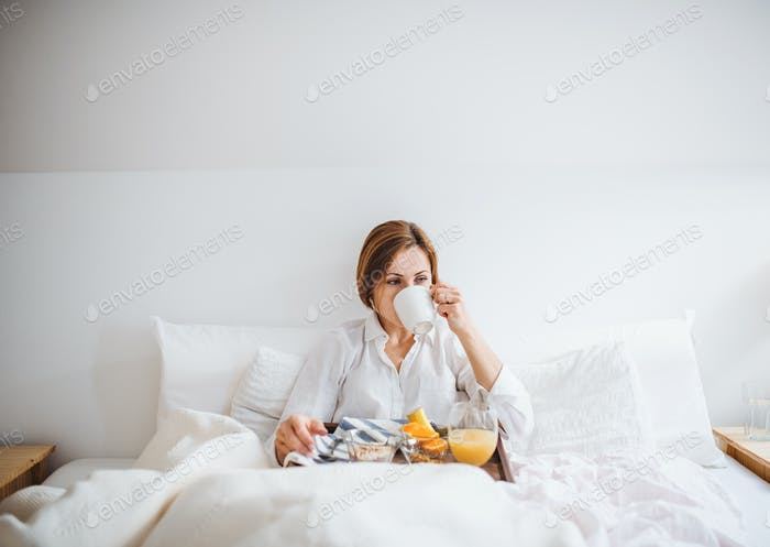 A front view of woman having breakfast in bed in the morning.