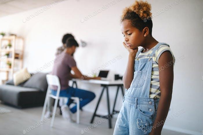 Traurig kleines Mädchen wartet auf beschäftigt Eltern Aufmerksamkeit zu Hause