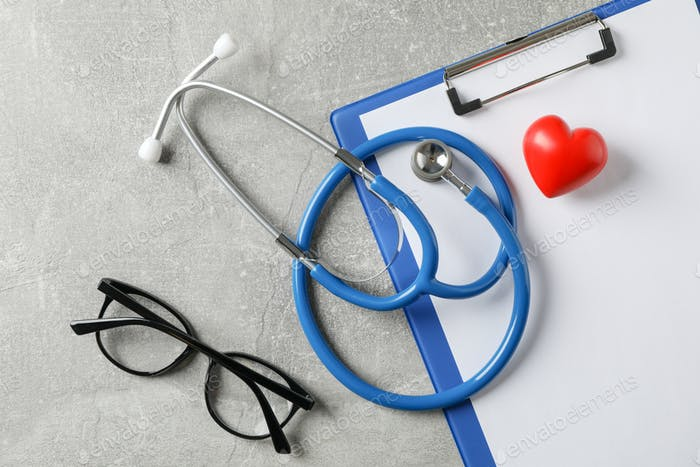 Stethoscope, heart, tablet and glasses on grey background, close up