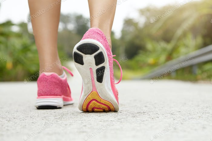 Cropped rear shot of athletic girl wearing pink sneakers while hiking or jogging on pavement outdoor