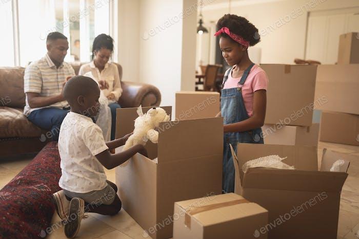 Niños afroamericanos desempacando sus pertenencias y padres sentados en el sofá en Página de inicio