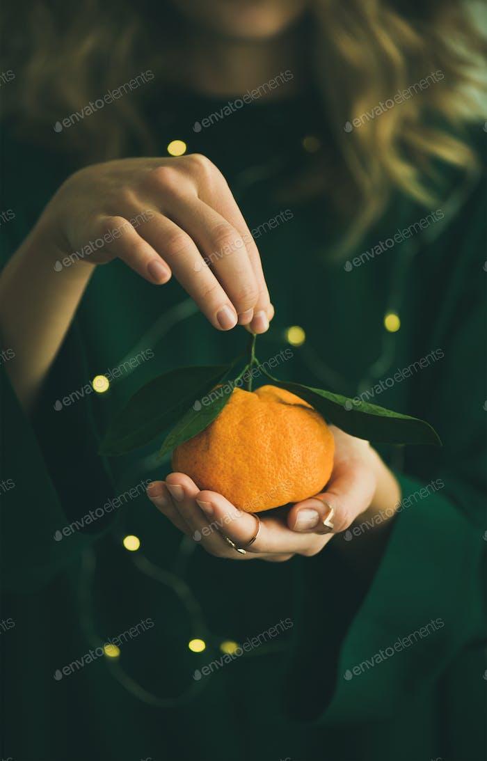 Fresh tangerine fruit in hands of girl wearing green dress