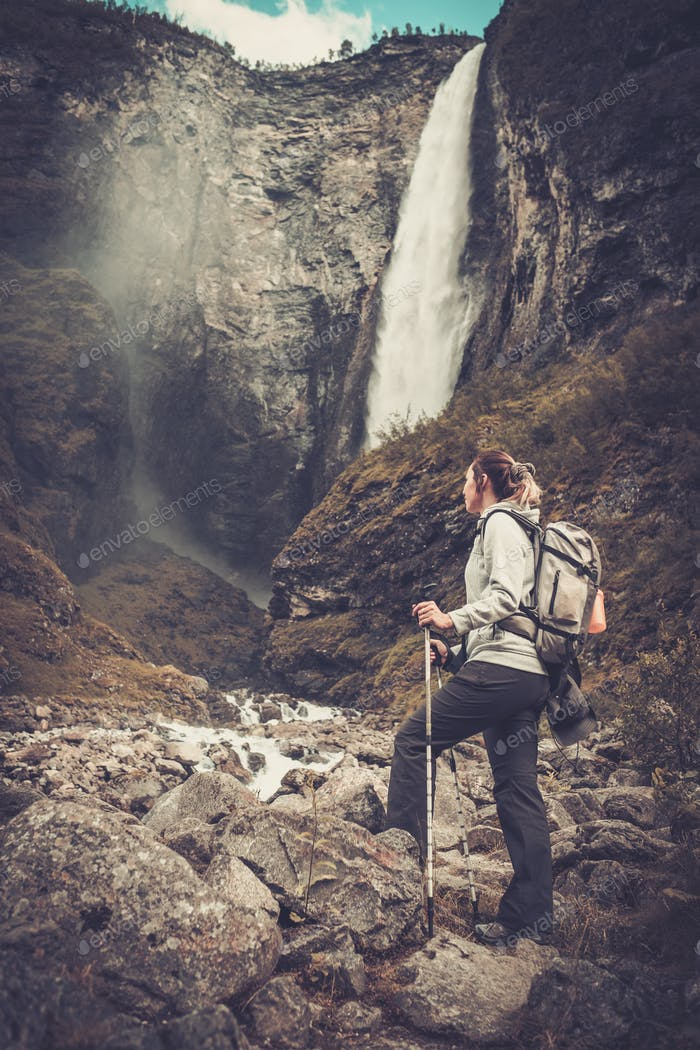 Woman hiker with backpack standing near Vettisfossen waterfall.