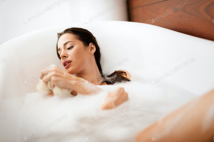 Beautiful woman taking care of her body in bathtub