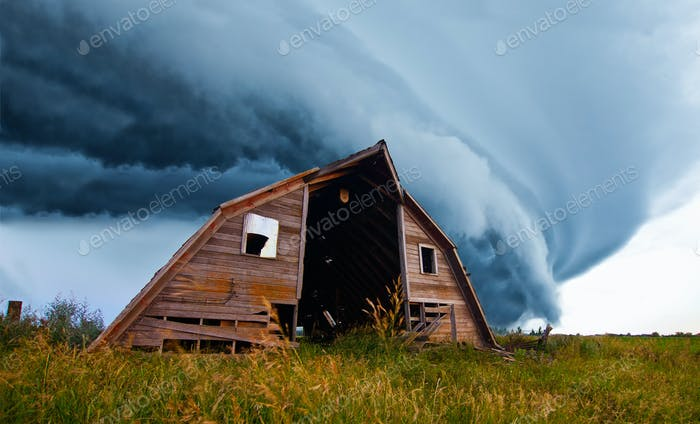 tornado forming behind old barn