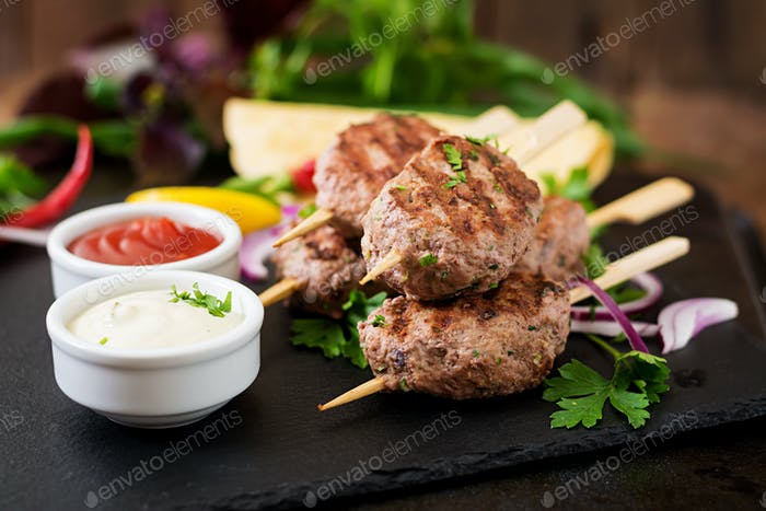 Appetizing kofta kebab (meatballs) with sauce and tortillas tacos on black background