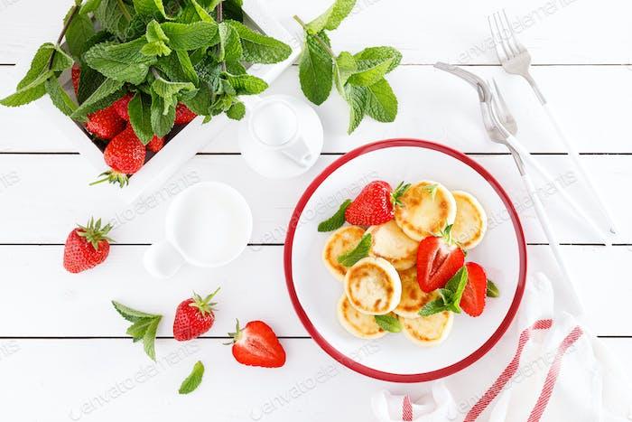 Käsepfannkuchen, Krapfen oder Syrniki mit frischer Erdbeere und Joghurt. Gesundes und leckeres Frühstück