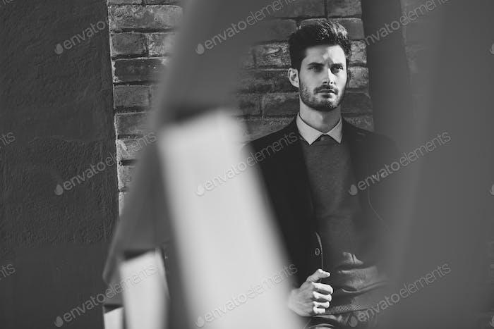 Привлекательный человек носит британский элегантный костюм на улице. Модер