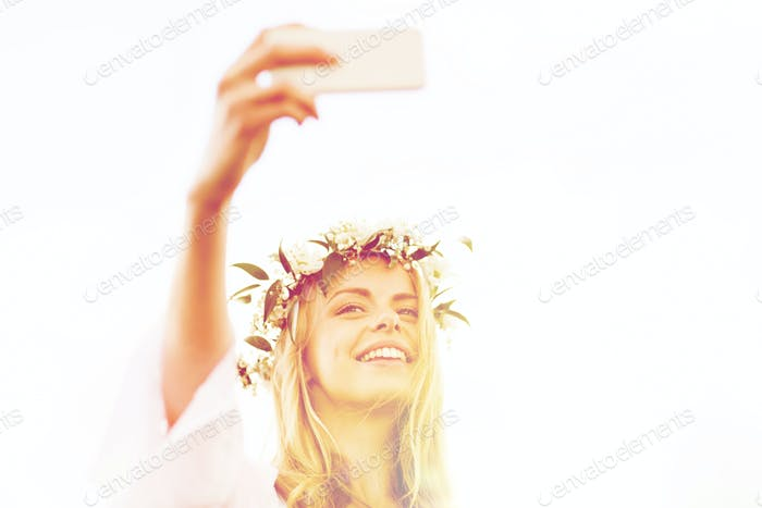 happy young woman taking smartphone selfie