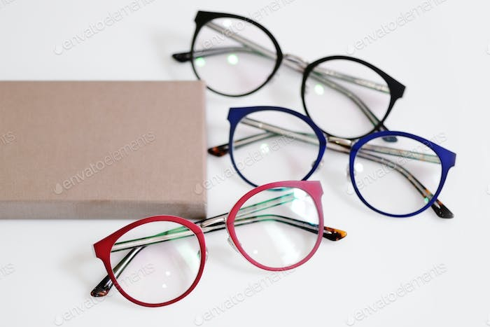 Multicolored fashionable glasses with box on white background