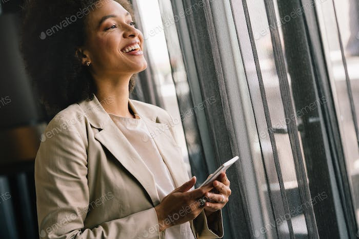 Portrait of a successful business woman using phone in office