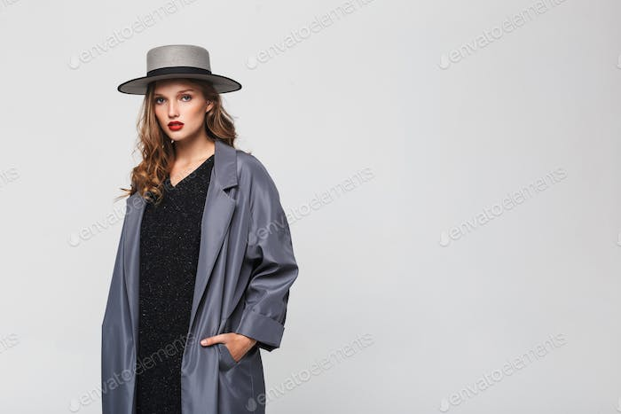 Stylish woman with wavy hair in hat and cloak holding hands in pockets looking in camera