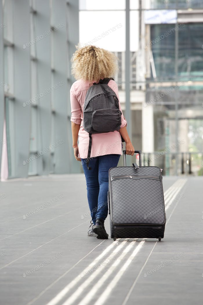 Young traveler walking away with suitcase and backpack
