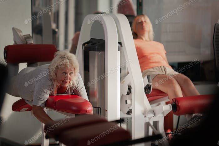Two middle aged women working out in a gym