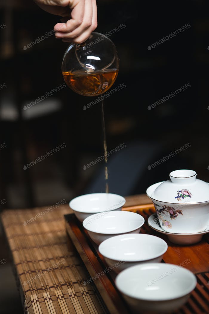 Hands pouring tea