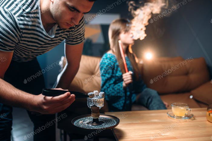 Young couple leisure at night club, smoking hookah