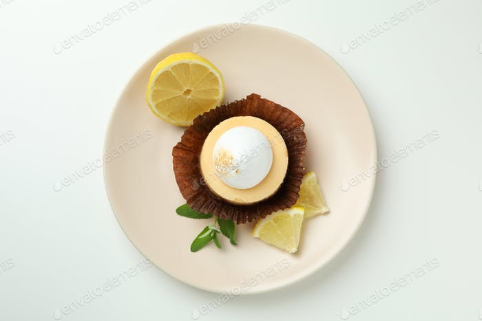 Plate with lemon cupcake on white background