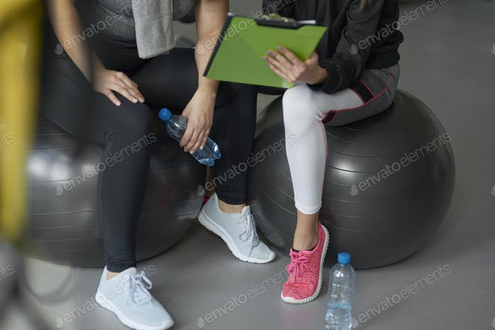 Personal trainer guiding sports woman