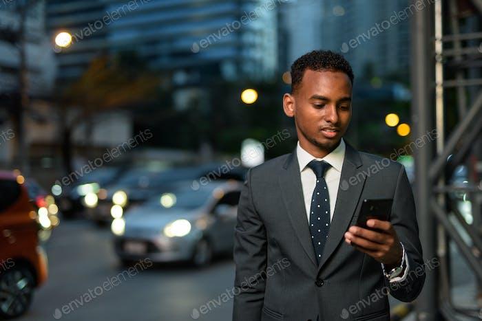 Afrikanischer Geschäftsmann nachts mit Handy