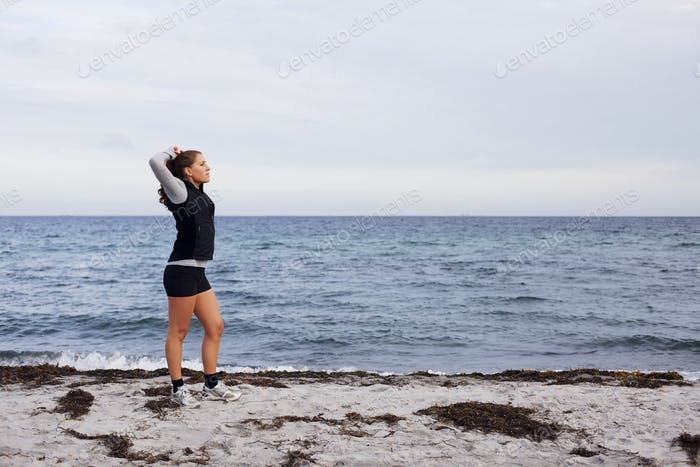 Sporty fitness woman standing on beach after workout