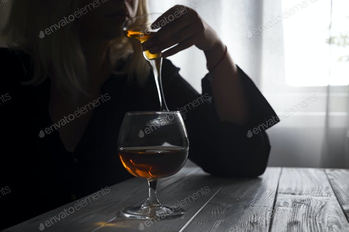 Woman drinking alcohol alone looking out her window. Depression, alcoholism, lonely person concept