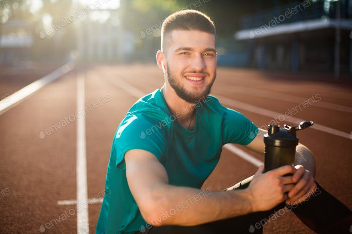 Young guy happily looking in camera holding sport bottle on running track of stadium