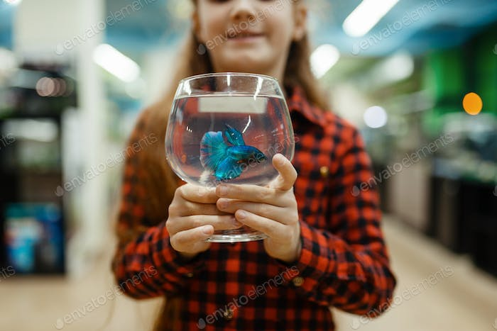 Little girl holds glass with blue fish, pet store