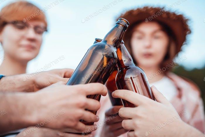 Friends clink brown beer bottles