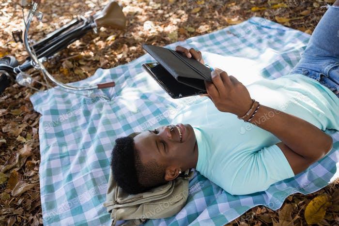 Mann mit digitalen, während auf einer Picknickdecke liegend