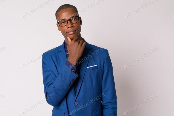 Portrait of young handsome bald African businessman with eyeglasses thinking