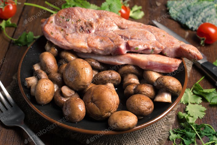 roasted turkey fillets mushrooms and other vegetables, on classic wooden board