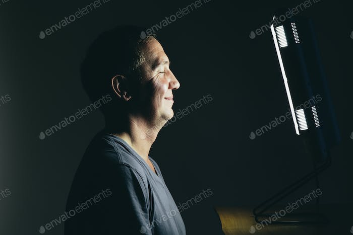 Smiling middle aged man sitting in front of a light therapy box.